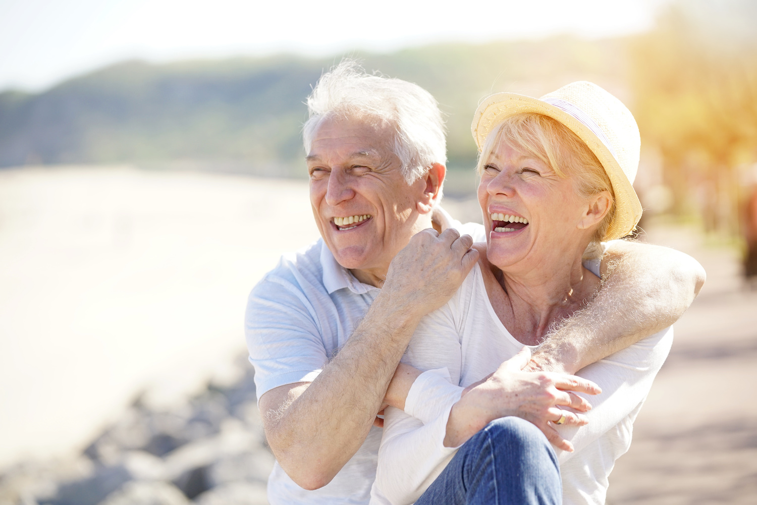 elderly couple laughing at the beach