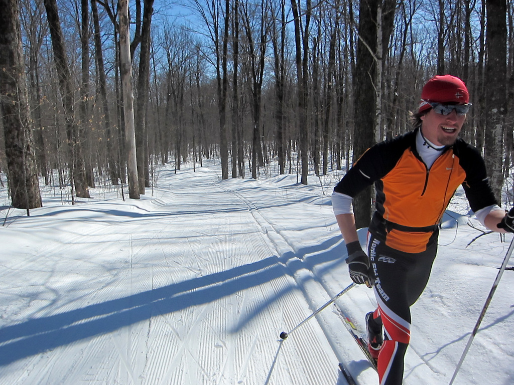 A cross country skier skis in the sun at the Blue Hills Trail in northwest Wisconsin