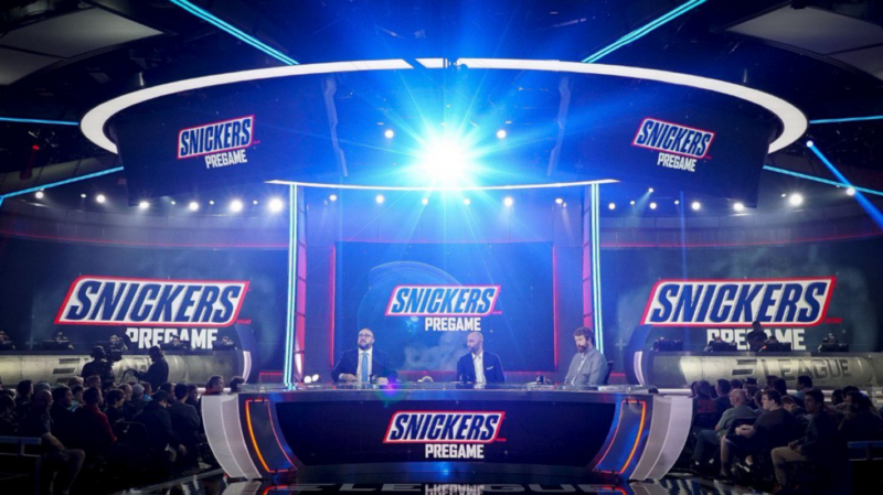 "Snickers has been advertising in esports for years. This image shows a studio in which announcers are covering ELeague's pregame. Featured six times is ""Snickers Pregame."""