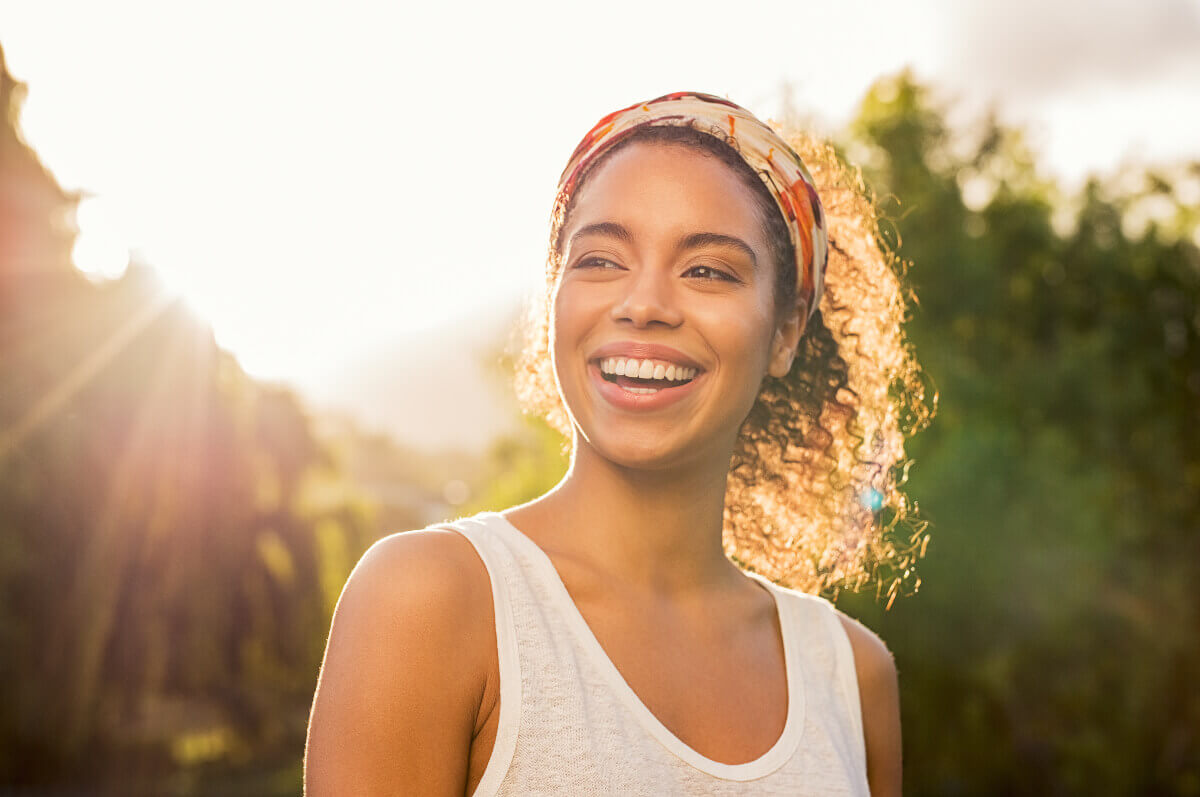 girl smiling in the sun with white teeth