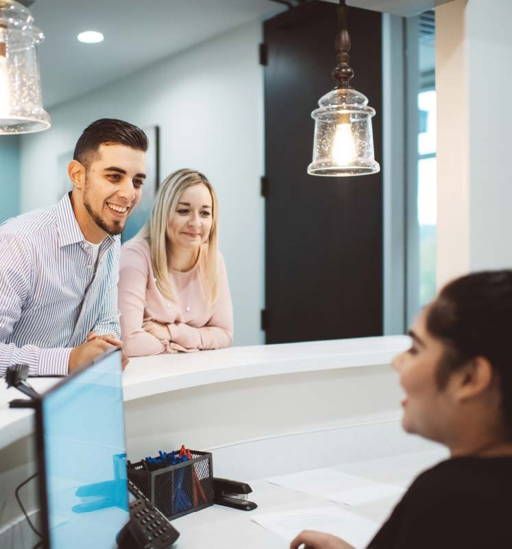 Photo of two patients talking with woman at front desk