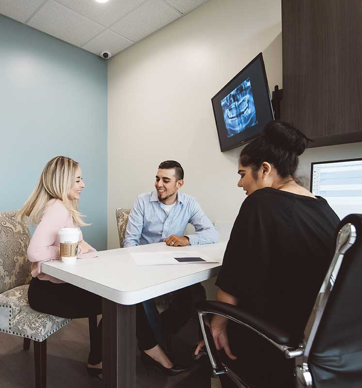 Photo of two patients talking with a team member at a desk