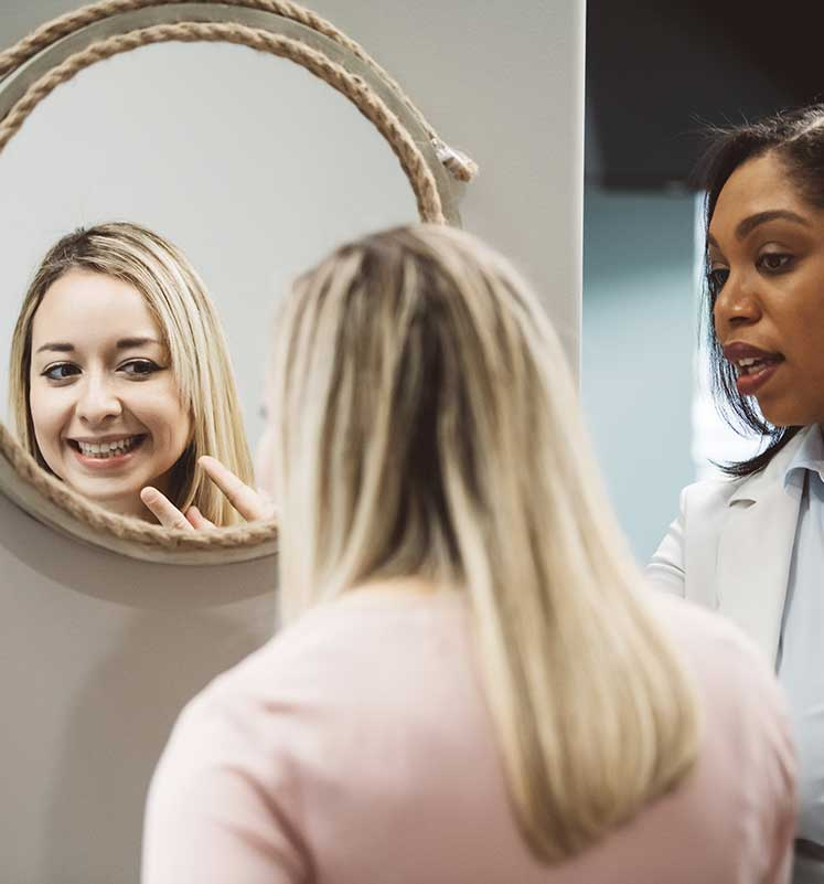 Photo of a patient looking at her smile in the mirror