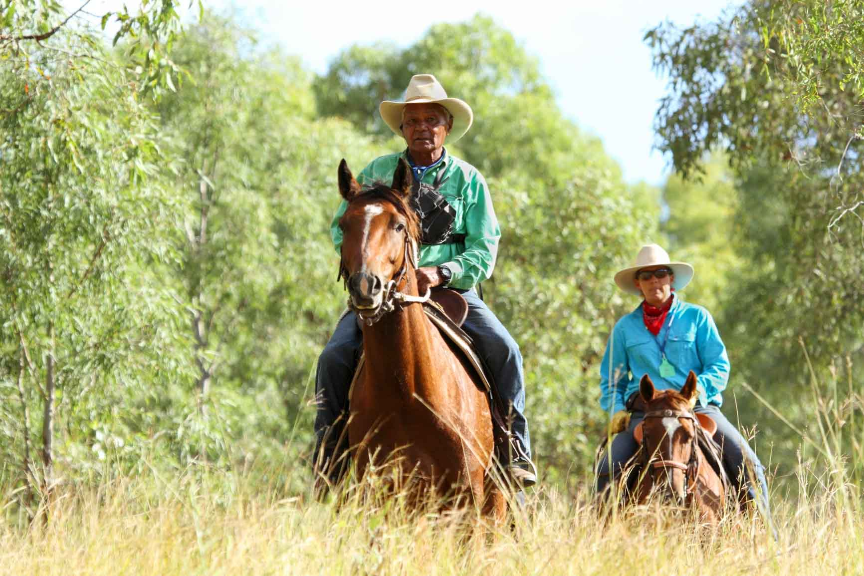 Two men of indigenous decent riding horses through Western Australian bush
