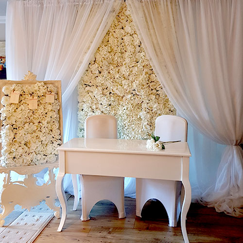 photo of a white desk in front of a wall of white roses