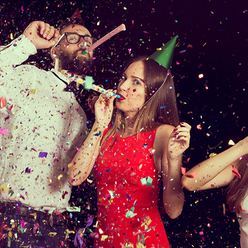 photo of two people blowing party trumpets
