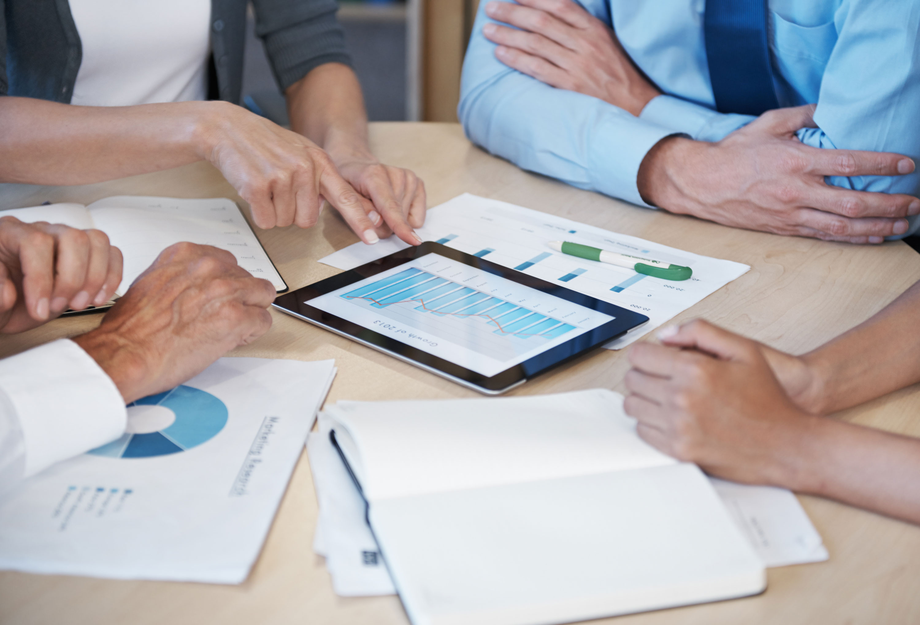 Business accountancy hero image of a financial meeting showing graphs and figures