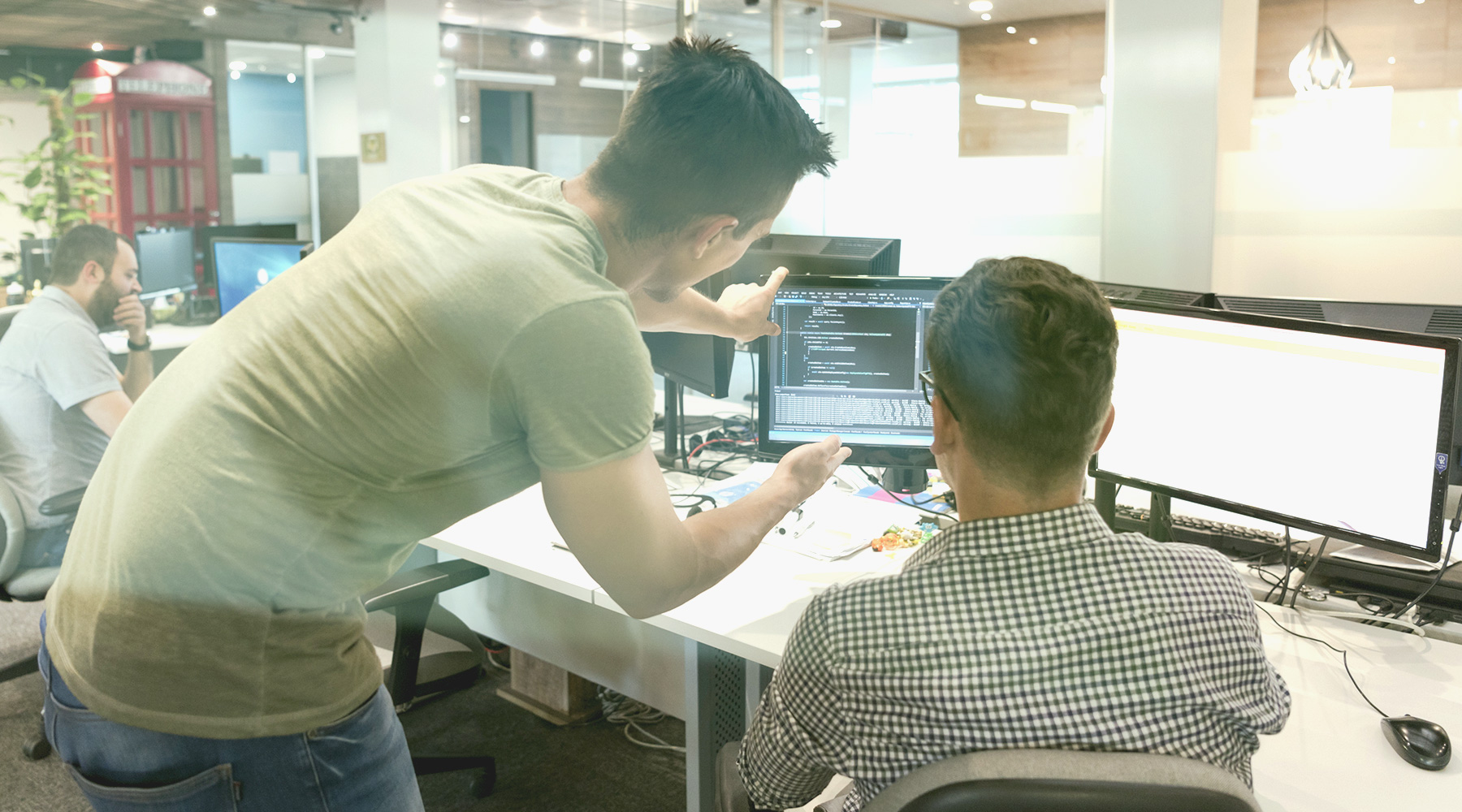 Two men looking at a computer screen at an office desk.