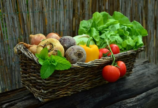 woven basket filled with fresh vegetables on a weathered wooden table