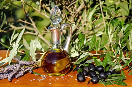 small vessel of oilive oil next to olives and olive tree vegetation