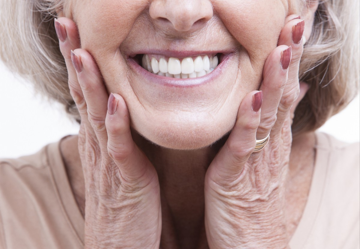 Patient smiling with full-arch dentures