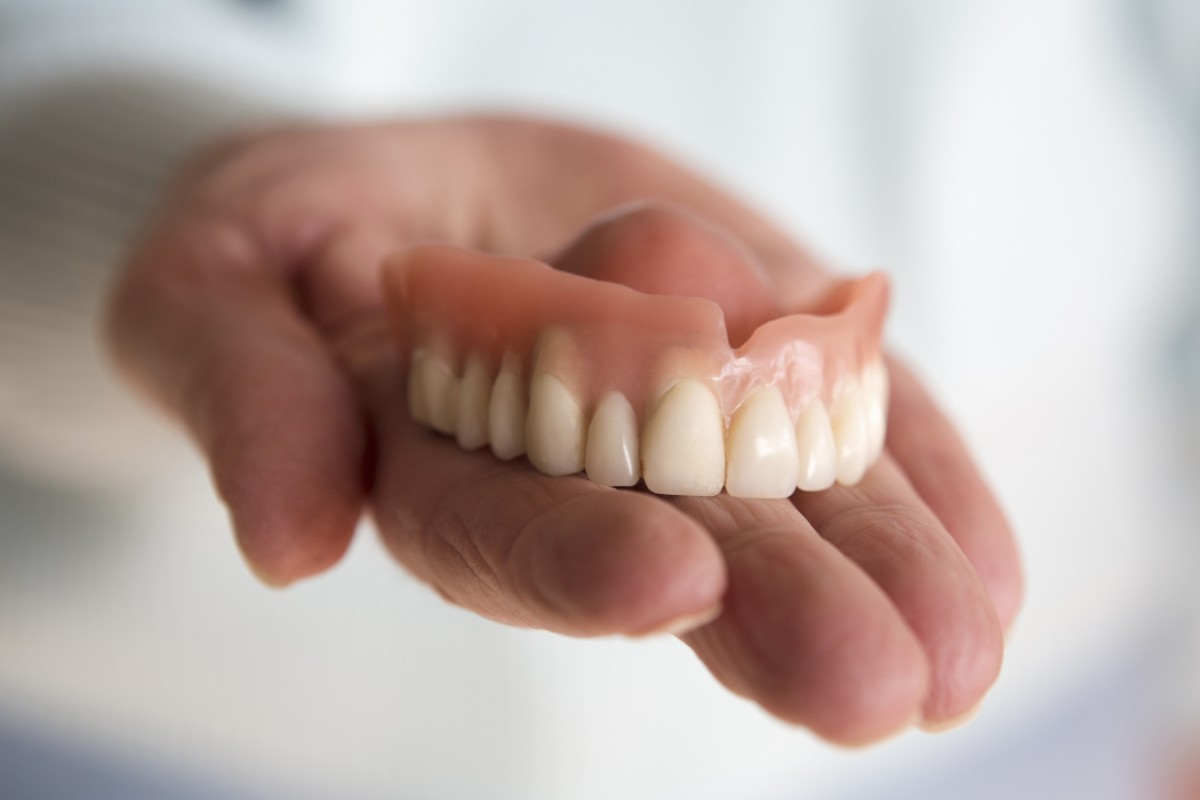 Hand holding dentures