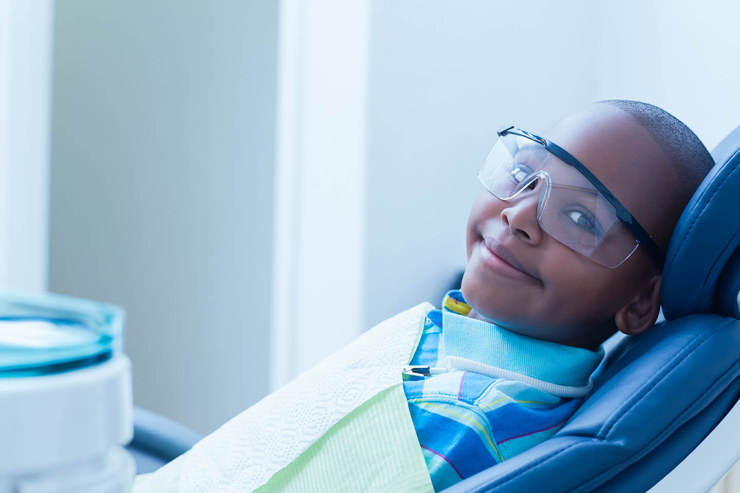 Child with goggles smiling in examination chair