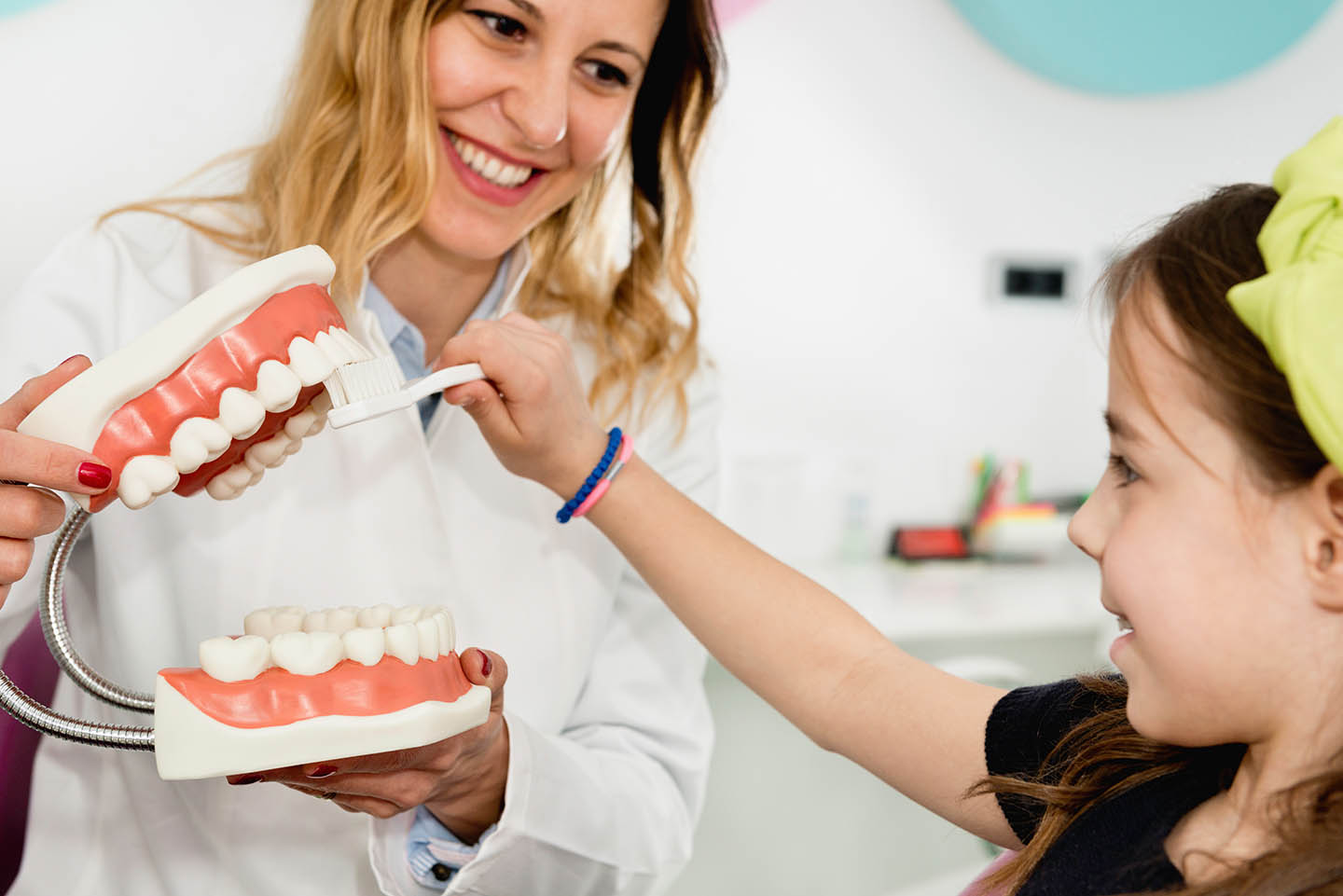 child brushing tooth model with dentist