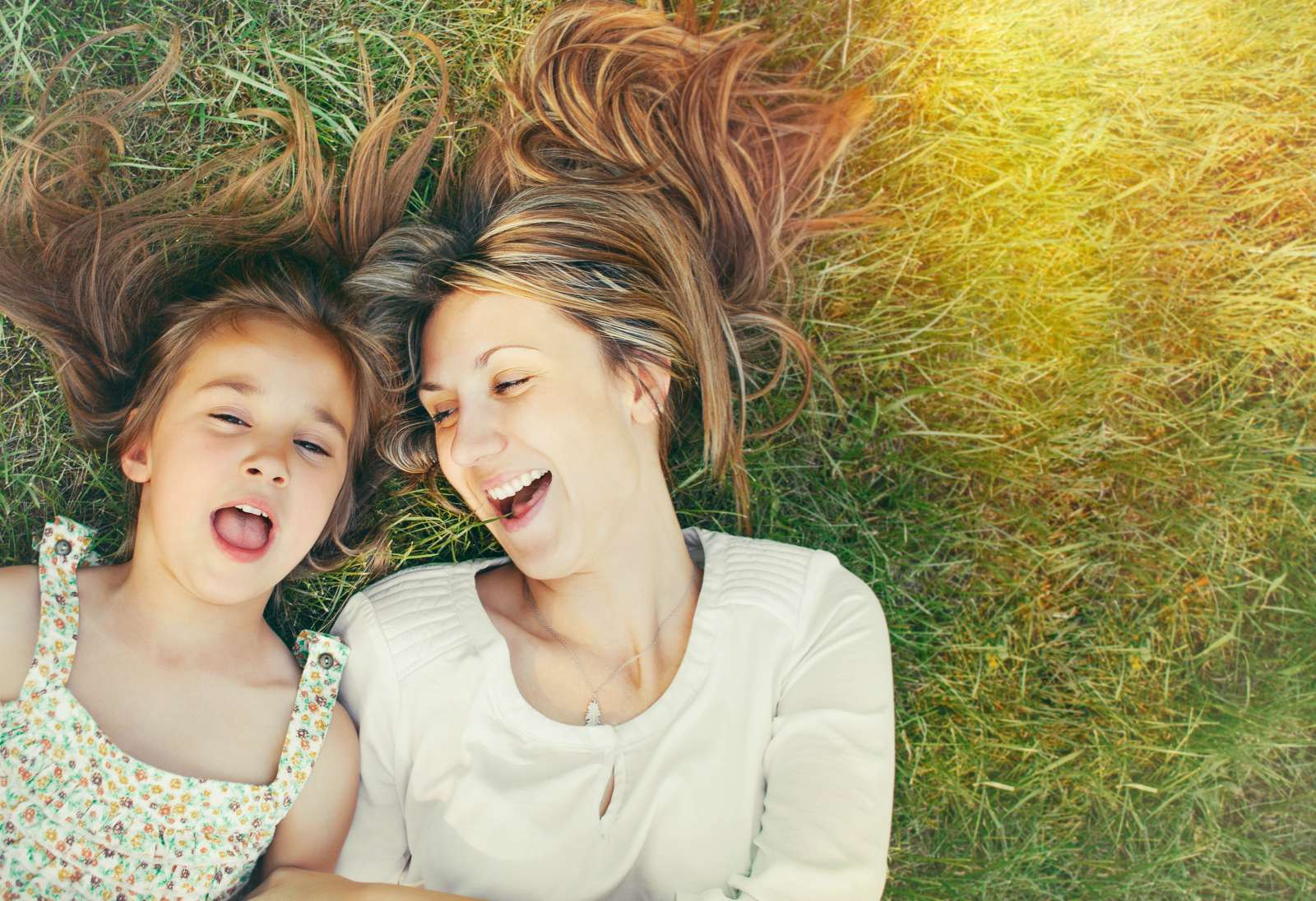 Mother and daughter laying in grass field and smiling