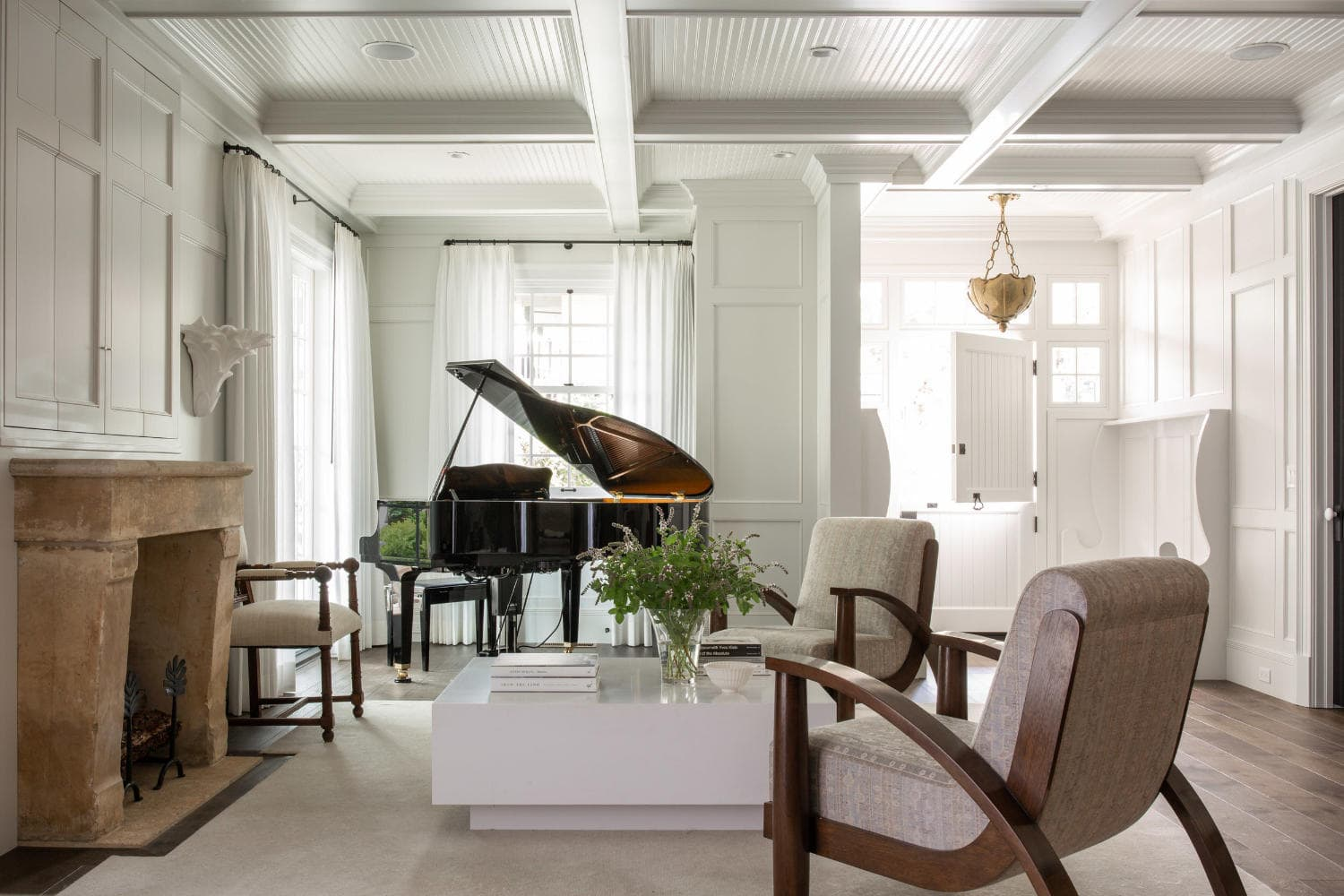 A living room with grand piano and lounge chairs, designed by Amy Meier.