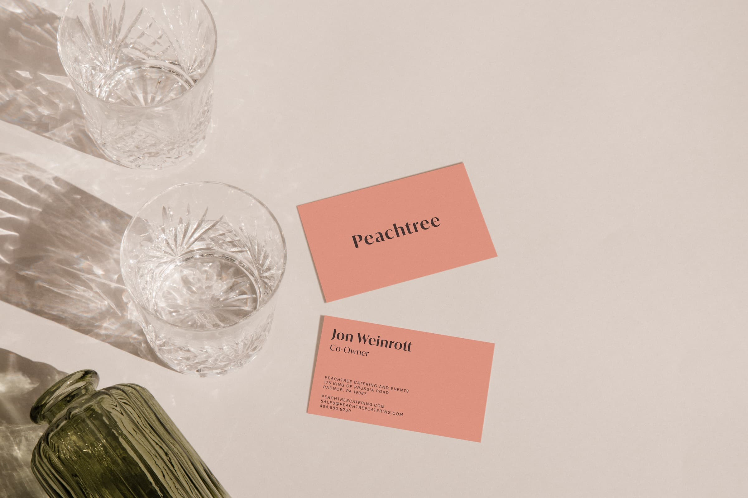 Peachtree business cards on a table, next to a few glass cups.