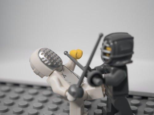 Two lego men sword fighting.