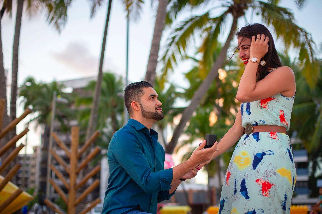 homem ajoelhado fazendo pedido de casamento na praia