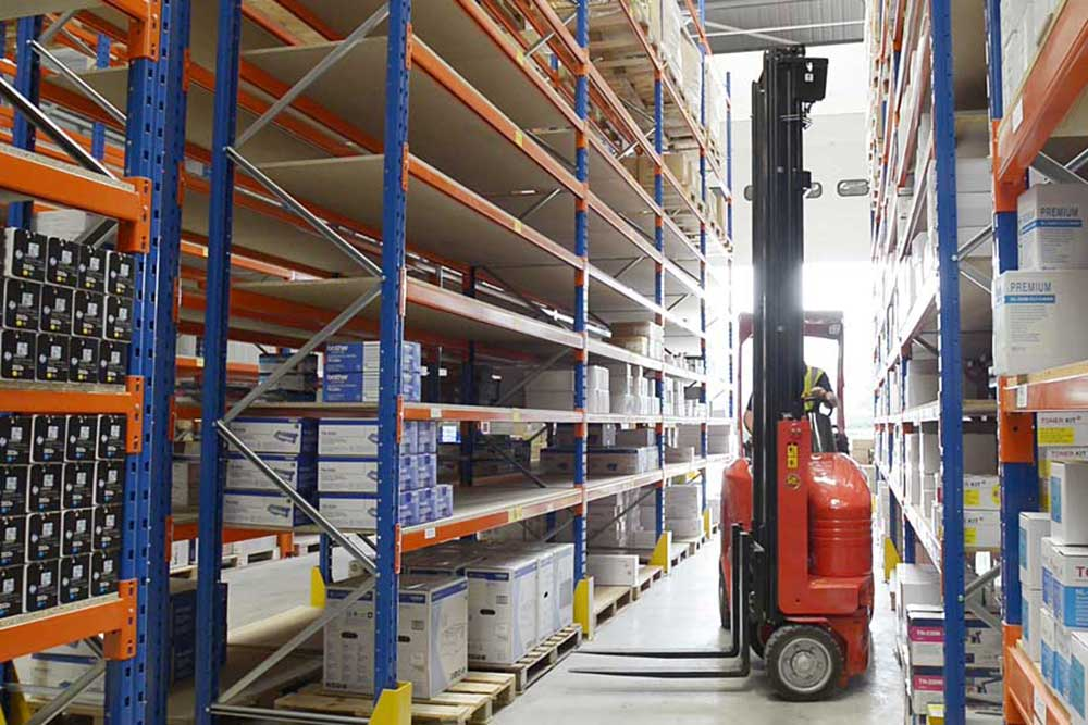 Red narrow forklift working down a big box Intralogistics  warehouse aisle