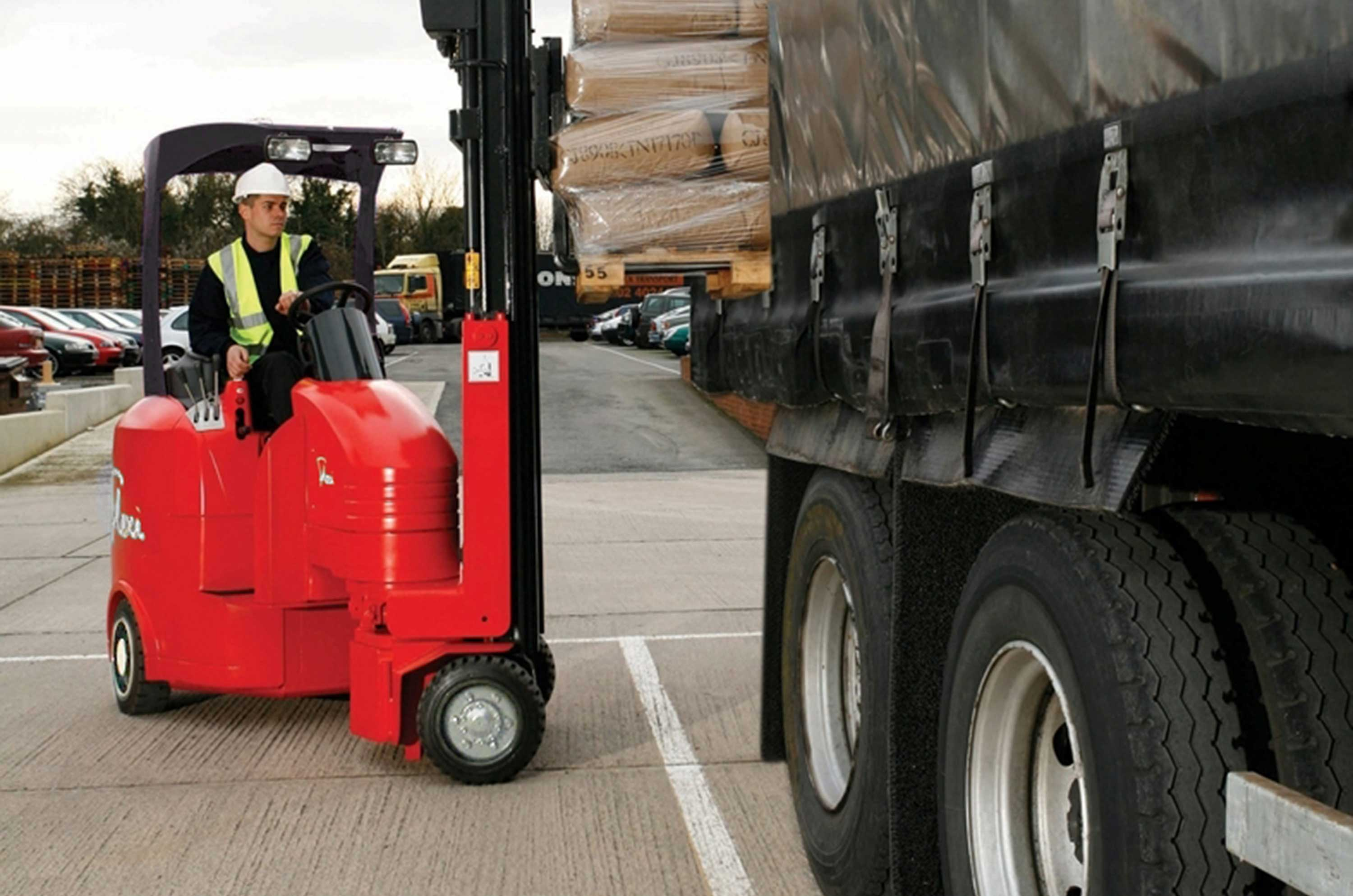 Red Flexi Fork Lift Truck loading a Lorry outside a Warehouse