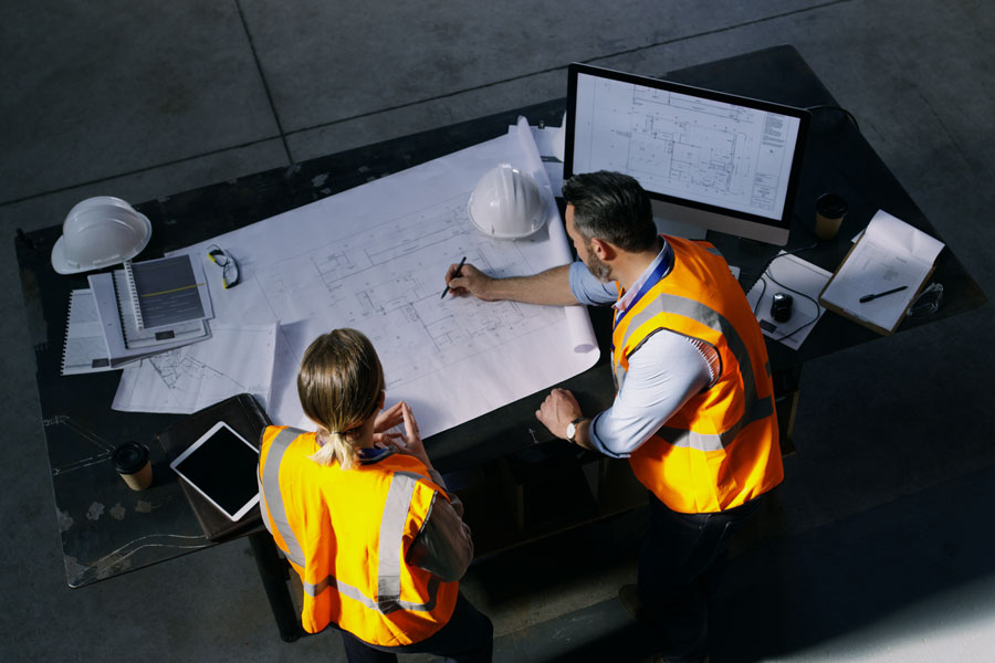 Two developers at a desk in front of warehouse plans