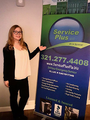 Jules standing next to Service Plus pull-up banner