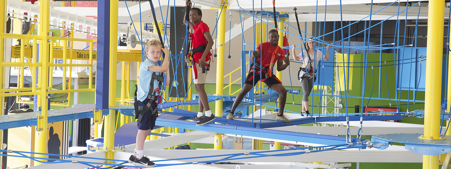 A kid is defying gravity on an indoor ropes course at Highmark Sportsworks
