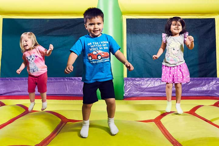 3 children are playing in a bouncy house