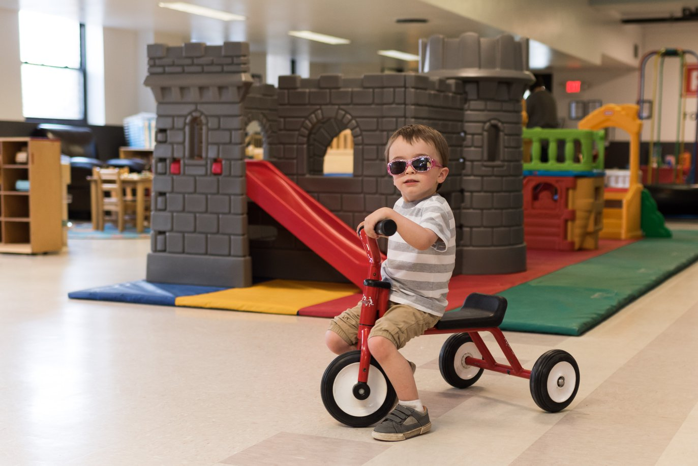 A boy wearing sunglasses is riding a tricycle at The Toy Lending Library
