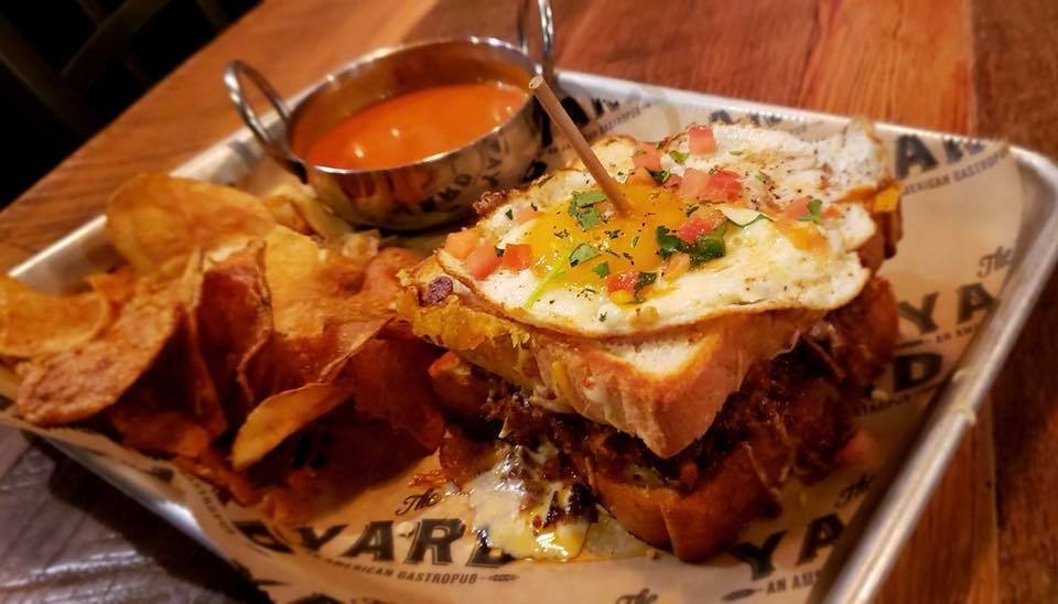 Tray of chips and grilled cheese topped with egg