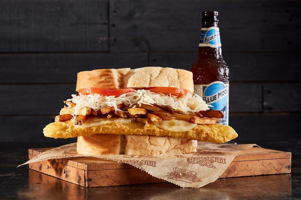 Primant's sandwich topped with slaw and fries, with Blue Moon beer