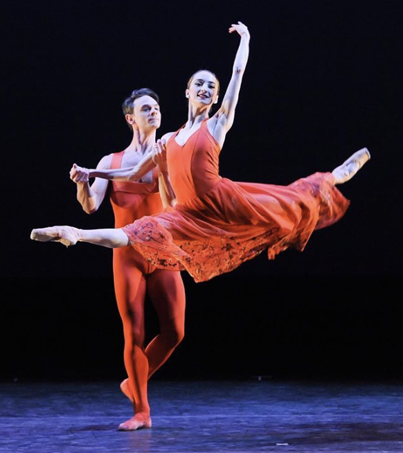 Female ballerina jumping with male dancer