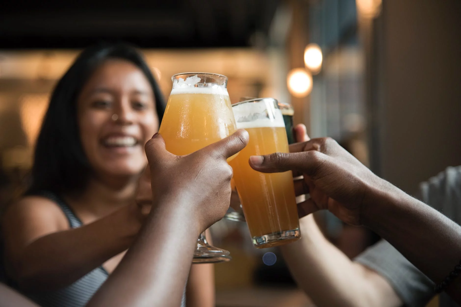 Friends cheers each other with glasses of golden beer