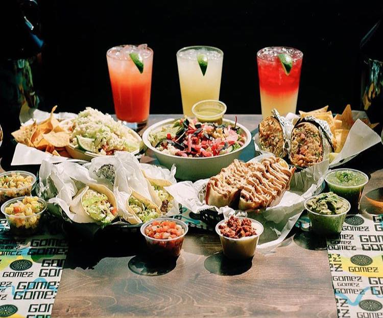 A spread of delicious mexican food: nachos agua fresca, guacamole, salsa and more