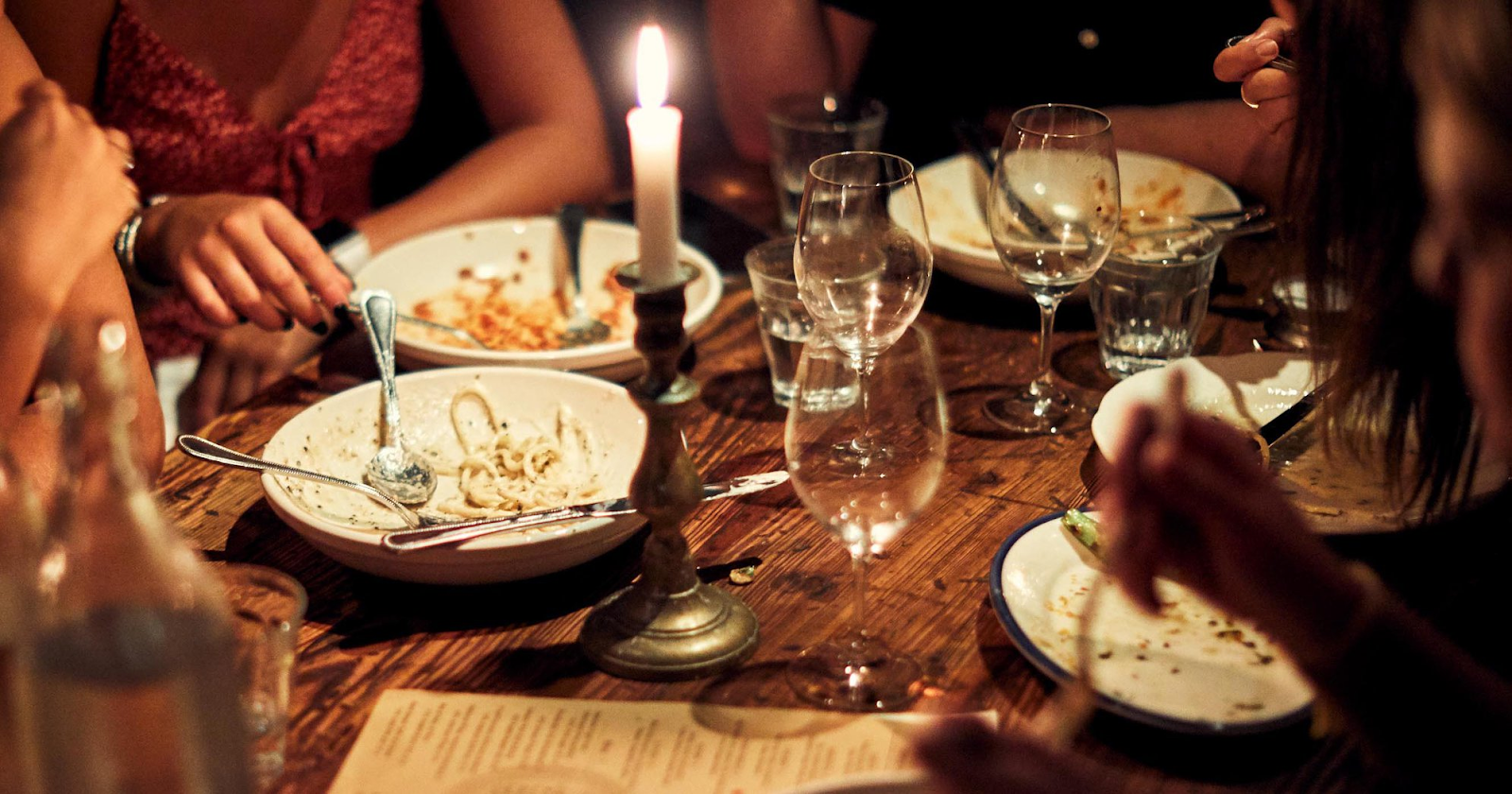 Intimate candleit dinner with plates of pasta