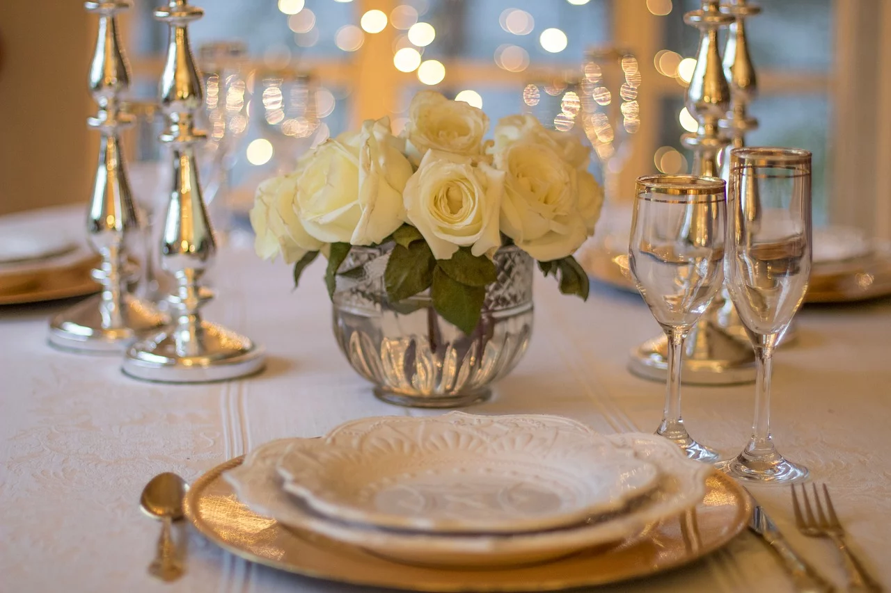 dining table with candles, flowers, white roses