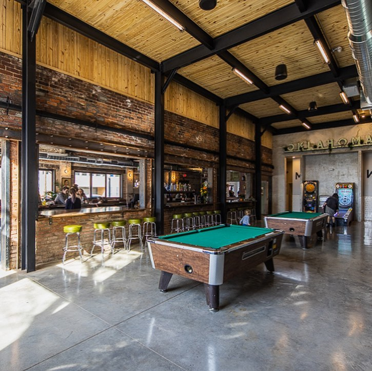 Two pool tables tall ceilings, green bar stools and a rustic atmosphere