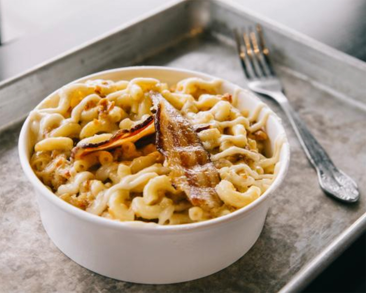 A hot bowl of cheesy macaroni and cheese with bacon. Bacon mac n cheese strips on top