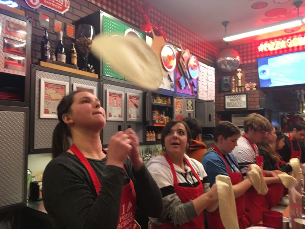 culinary class tossing pizza dough on an educational new york trip