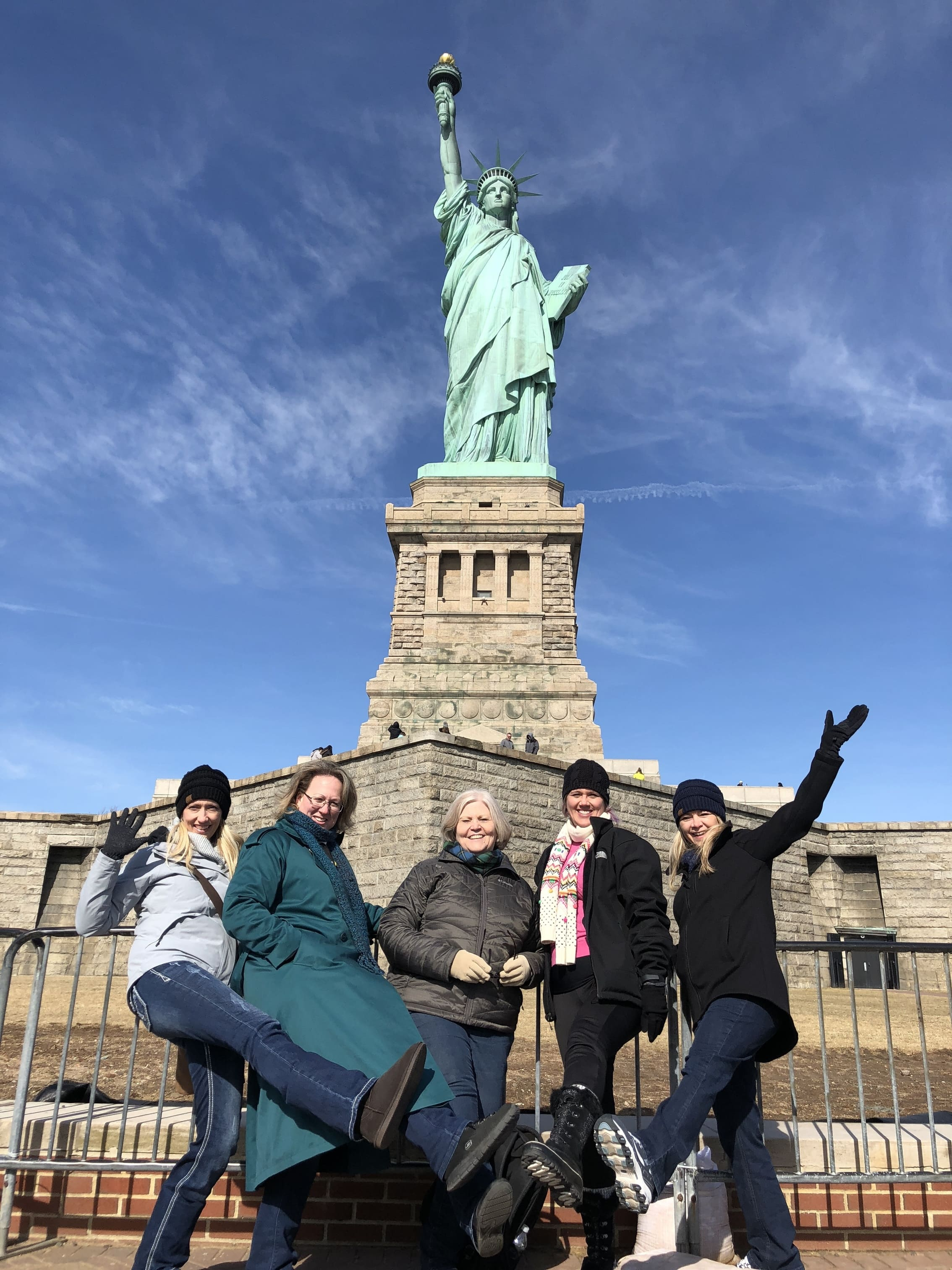 fbla and deca teachers posing in front of the statue of liberty during a new york student trip