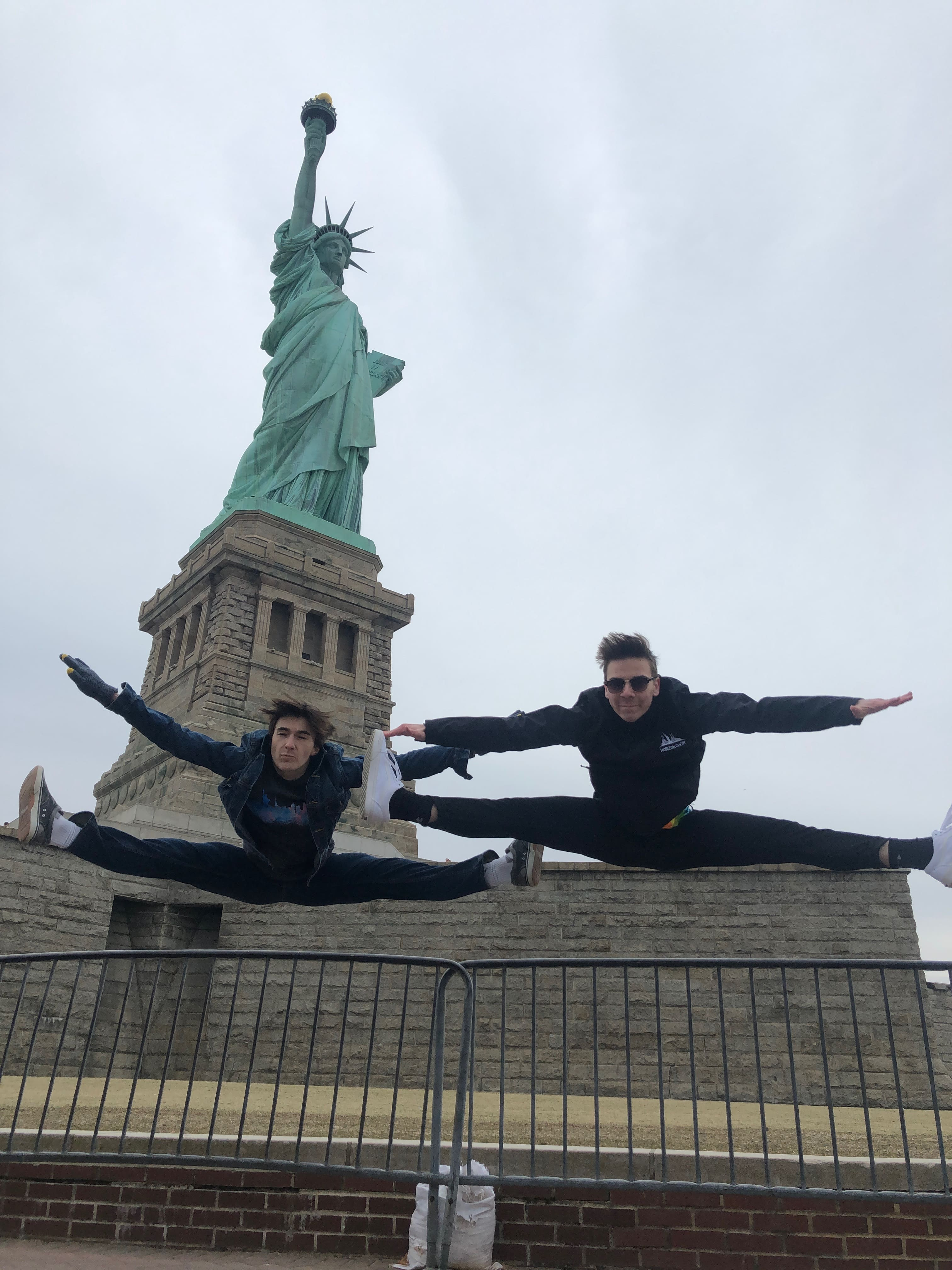 dance students doing a flying split in front of statue of liberty during new york student trip