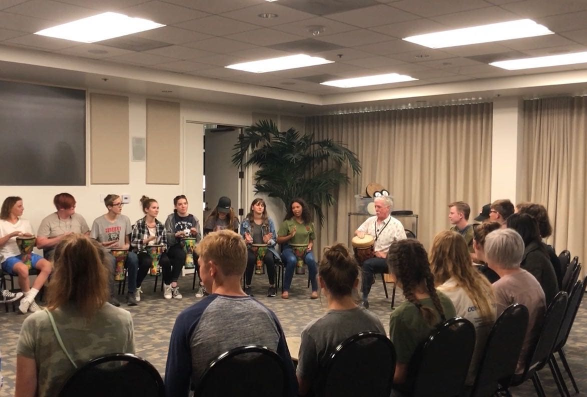 band students performing a drum circle during their educational trip