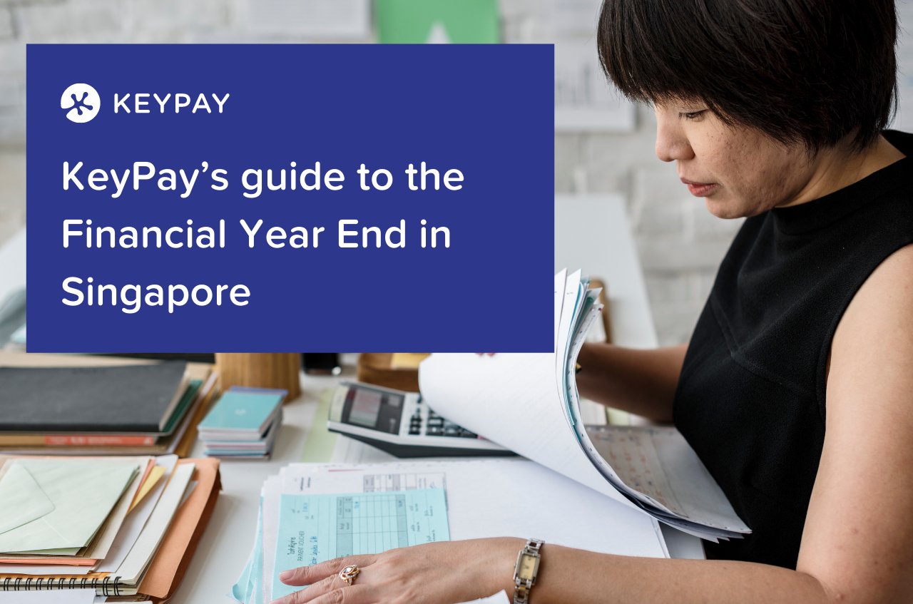 A Southeast Asian woman in a black shirt is looking through a pile of payslips at her work desk. The text overlaid on the top left hand side of the picture says KeyPay's guide to the Financial Year End in Singapore