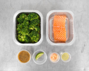 Raw salmon filet and edamame brown rice in Tovala Meal trays with garnishes in cups.