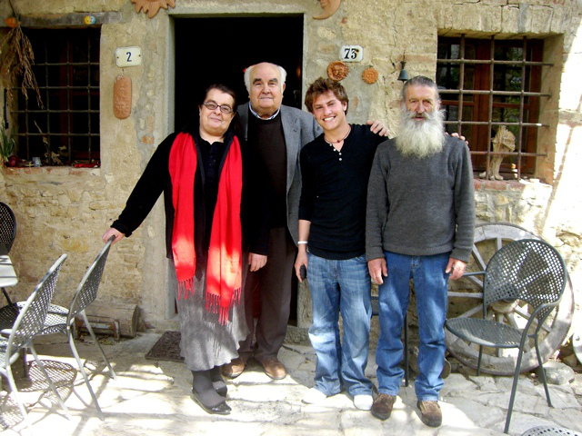 Chef Plotkin and three men stand in front of a house in Italy.