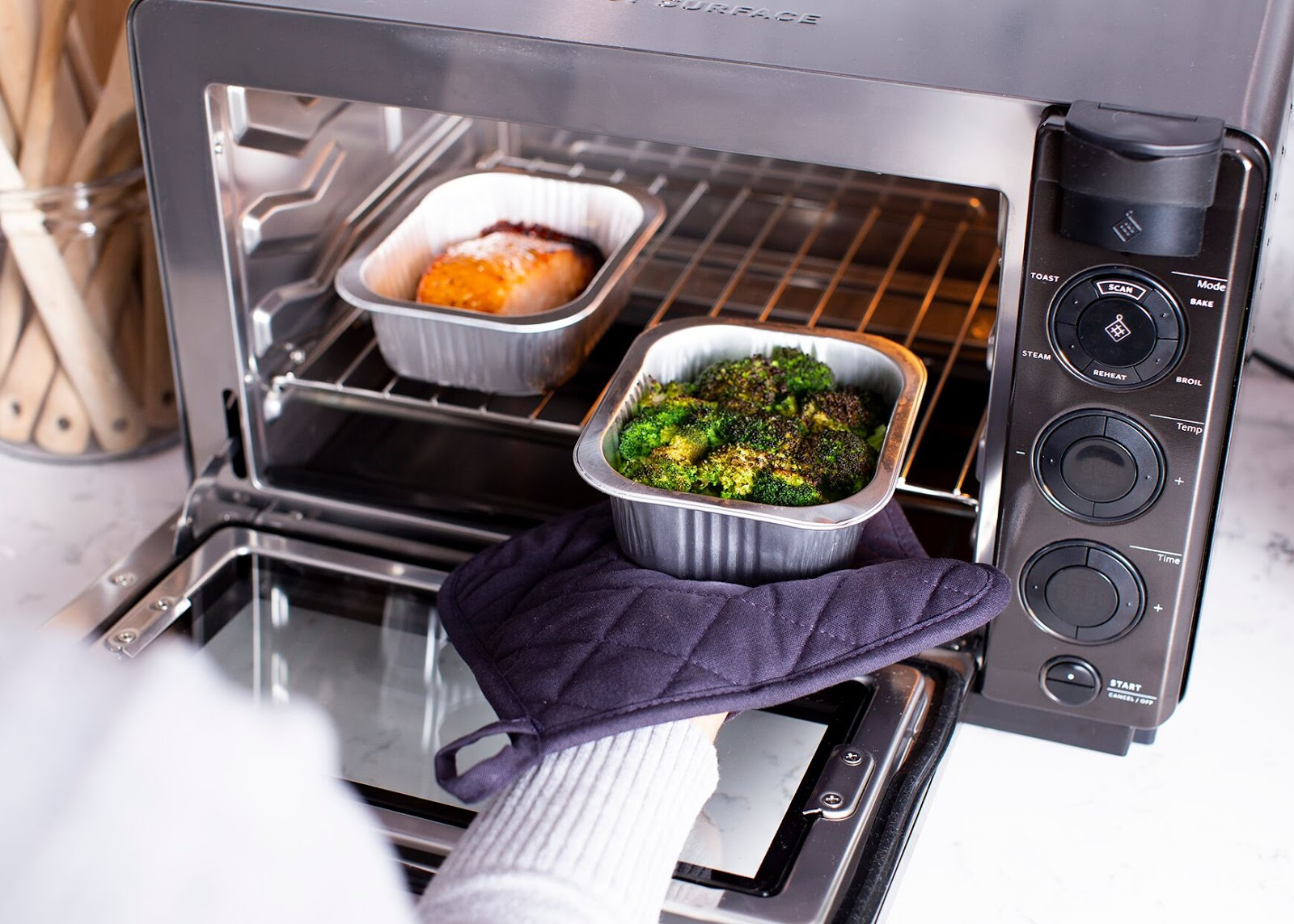 Countertop oven: A woman takes food out of the Tovala Steam Oven
