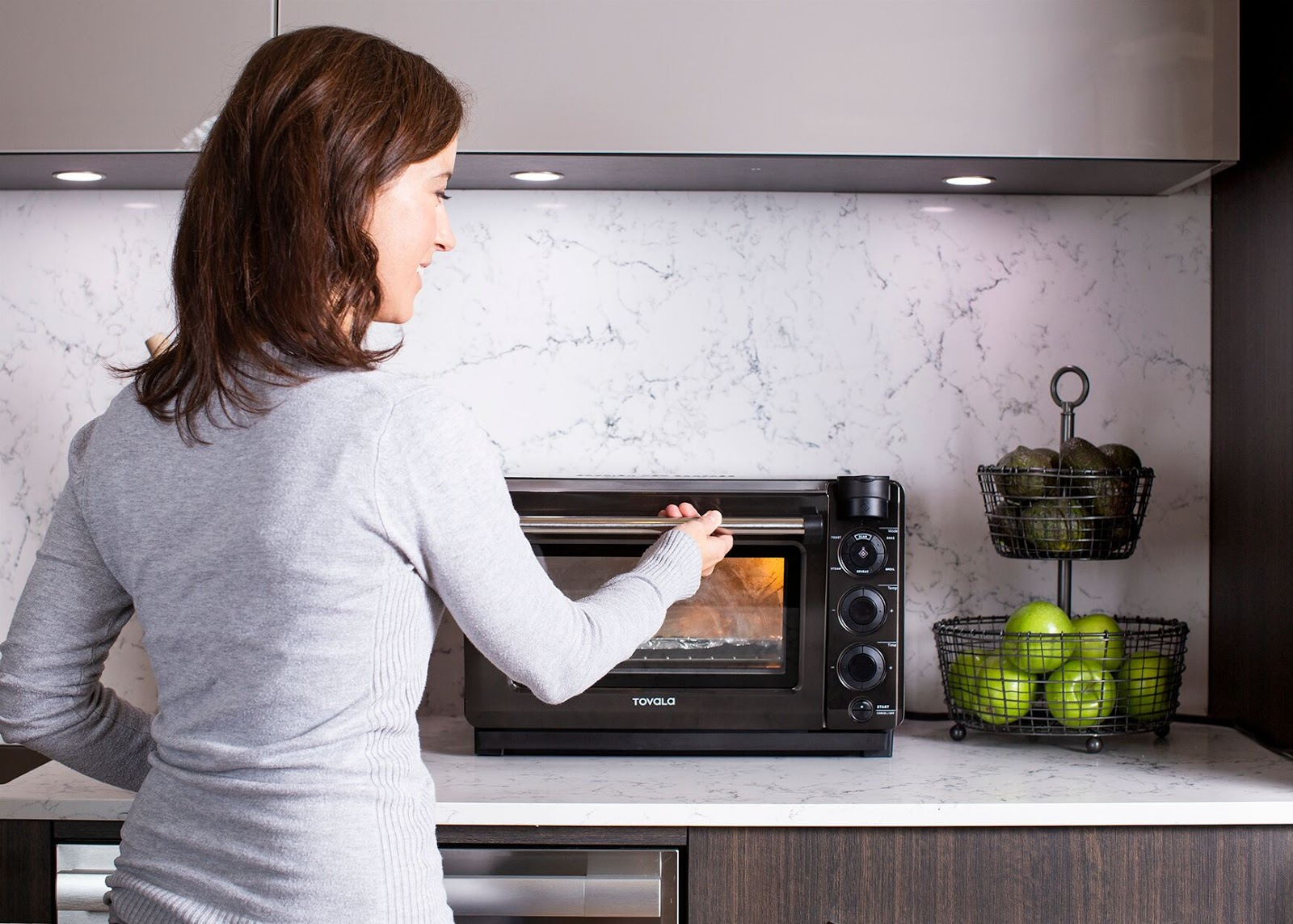 Countertop oven: A smiling woman opens a Tovala Oven
