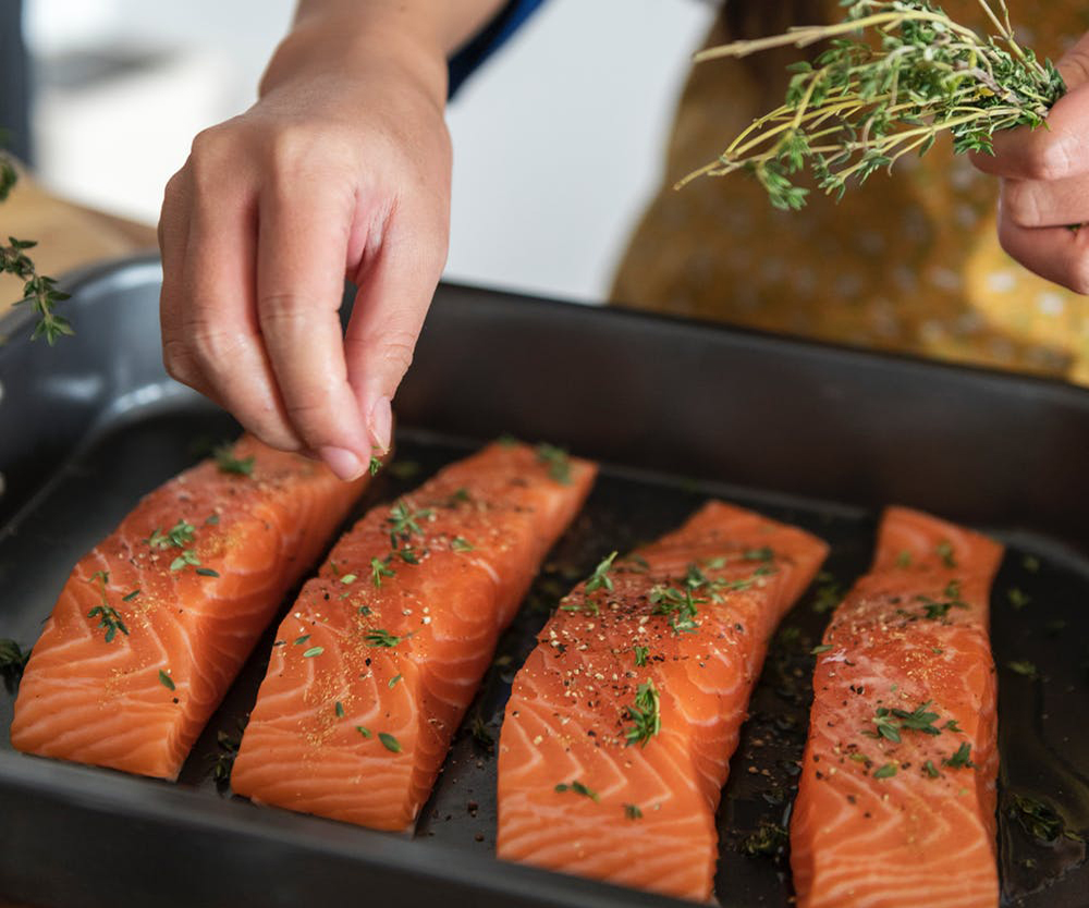 Easy healthy dinner recipes: A woman prepares salmon on a sheet pan