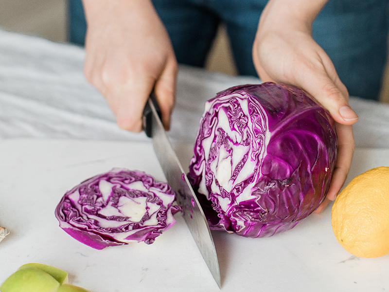 Plated meals: A woman chops red cabbage
